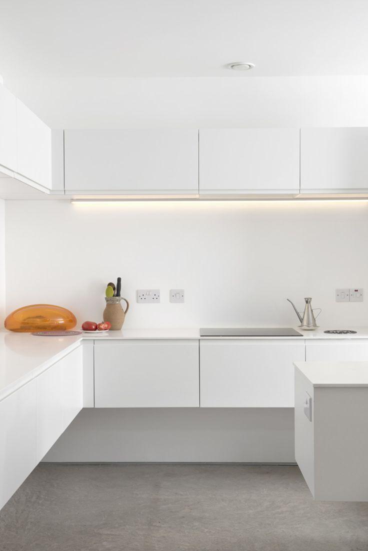 The stark white minimalist kitchen features quartz countertops, a Gessi Oxygene tap, a 1810 Company Zenuno sink, and energy-efficient Bosch appliances.