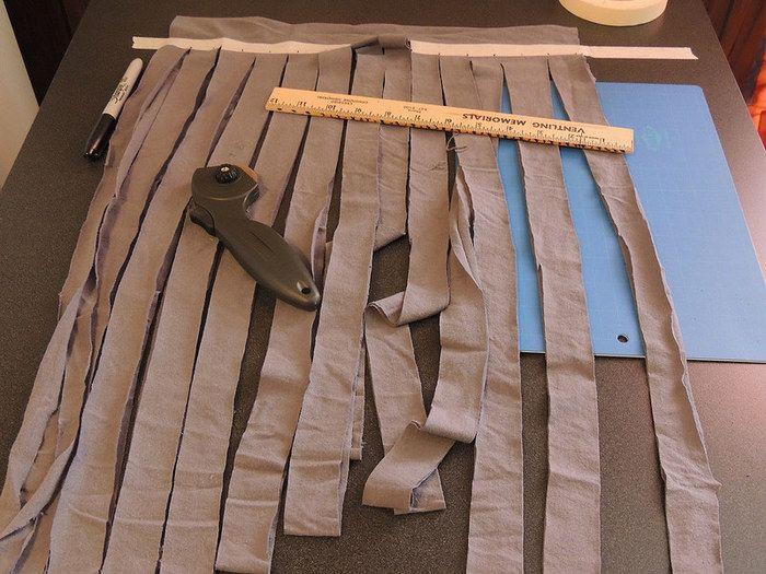 Tシャツの胴体部分からハサミを入れ、5cmほどの幅で切っていきます。 糸状にするため、胴体の端部分は切らずに残しておきます。 袖の下部分までカットし、袖から上、また裾の縫い目部分も切り離し、そちらは廃棄します。 切れ目を入れなかった胴体部分を手に取り、切れ目の端から一つとなりの切れ目の端までハサミを入れます。 こうすることで一本の長い糸状になります。