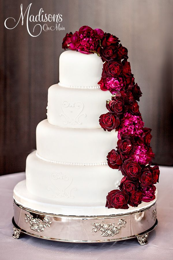 Fresh flower cascade..... - This bride and groom chose a clean and simple fondant cake with a dramatic fresh flower cascade. The top and third tier were smooth with an edible pearl border.  The second and bottom tier had a pattern that mimicked the bride's gown.  I created a cascade, using dark red roses, and red peonies!