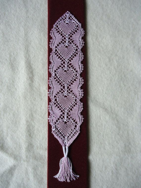 This bookmark is made using traditional bobbin lace patterns in pink cotton thread and 22 pairs of bobbins. The central heart pattern and the outer