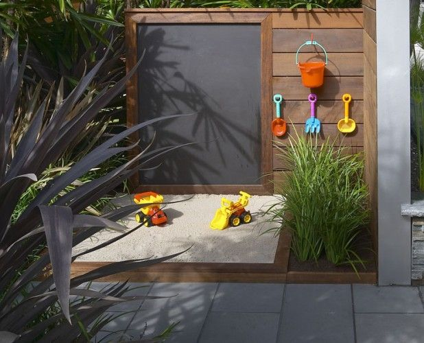 Kid corner in the backyard with sandbox, outdoor chalkboard, and hooks for hanging toys
