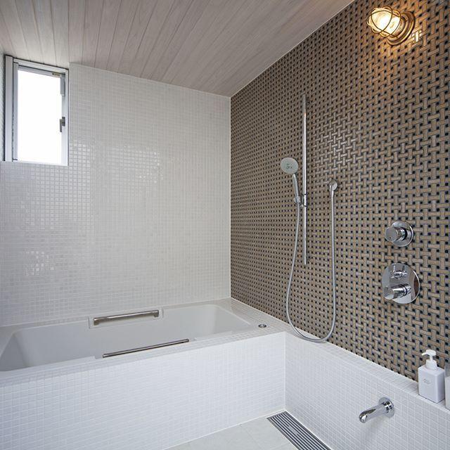 壁のタイルが印象的なバスルーム。レインシャワーも設備されてます。 #注文住宅#kisetsu#マイホーム#シンプルな家#おしゃれな家#浴室#浴室タイル#バスルーム#レインシャワー#建築#設計事務所#浴槽#明るいお風呂#お風呂#庭#ナチュラルな暮らし#窓のあるお風呂#モダンな家#ウッドデッキのある家#お風呂場