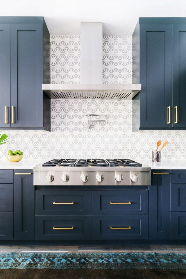 Kitchen with dark blue cabinents, gold fixtures,  dove gray tile, a stove hood, and a jewel-tone vintage runner