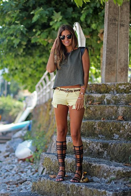 Shop this look on Lookastic:  http://lookastic.com/women/looks/crew-neck-t-shirt-shorts-knee-high-gladiator-sandals-belt-sunglasses/11147  — Charcoal Crew-neck T-shirt  — Tan Leopard Suede Belt  — Yellow Denim Shorts  — Black Leather Knee High Gladiator Sandals  — Black Sunglasses