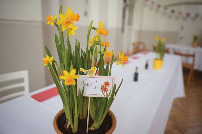 Potted flowers like these miniature daffodils make gorgeous budget table centres - plus you can use them as gifts afterwards! For more of Chris and Juliette's fab real-life wedding, click here! #weddingideas