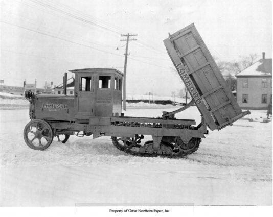 Historic Lombard hauler with dump body on tracks.