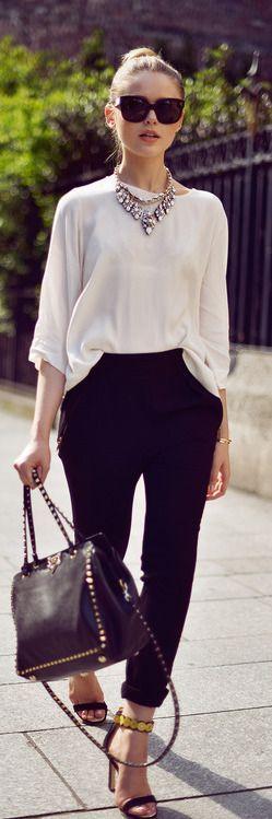 Blusa branca de manga longa, calça preta, colar de diamantes e salto