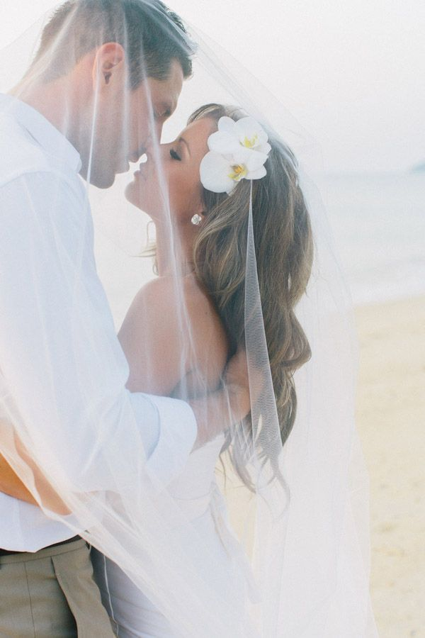 Gorgeous veil shot on the beach! Love the orchids in her hair too!
