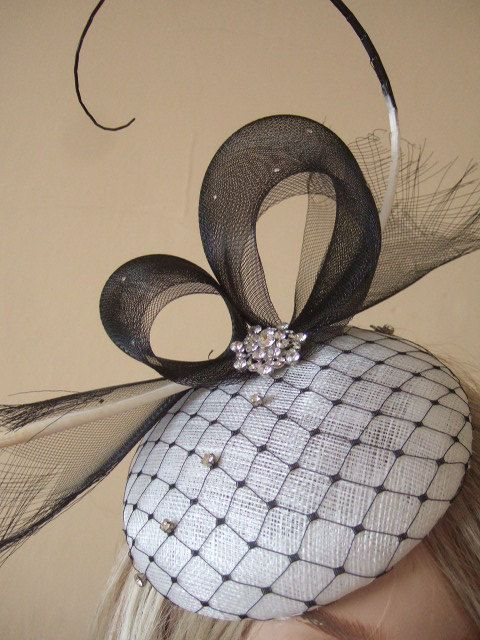 Beautiful Hand Made Fascinator in Black and White with Crystals White Button Base, covered with Black Merry Widow Veil, and decorated with a double twist of Black Frayed Crinoline at the Back, a Curled Ostrich Quill graduated from Black to White, and a Large Crystal Brooch at the