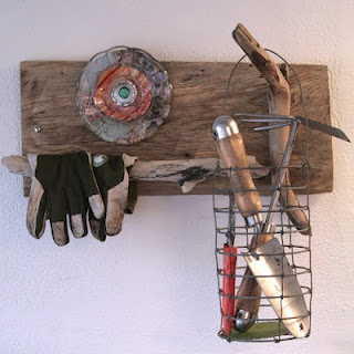 """My """"grab and go"""" garden rack for the garage. Made with a reclaimed board, 2 pieces of driftwood, an old wire basket, and some little glass plates with magazine pages mod podged on the back (to look like a funky little flower). It got featured on HGTV.com."""