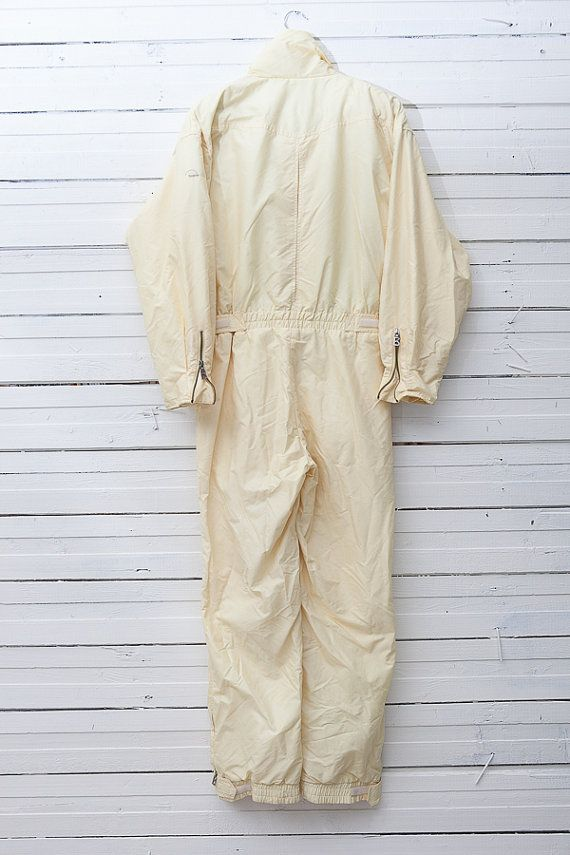 Yellow Snow Suit / 1980s Pale Yellow Skirwear Onepiece Snow Suit / Size S Small / Women Snowboarding Clothing / Snow Overall  A very girlie pale yellow ski suit. A metal zipper runs in the center of the suit. High collar. Elastic and belted waist. There are zipped pockets on the sides and on the chest. Inside lining is yellow and checkered with white/grey. ♔♔♔ BRAND: Bogner. Material: polyamid / poyacryl. Lining is 50% polyamid / 50% cotton. Filling is 80% a...