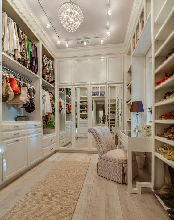 heavenly walk-in closet with a vanity and shoe and purse storage: