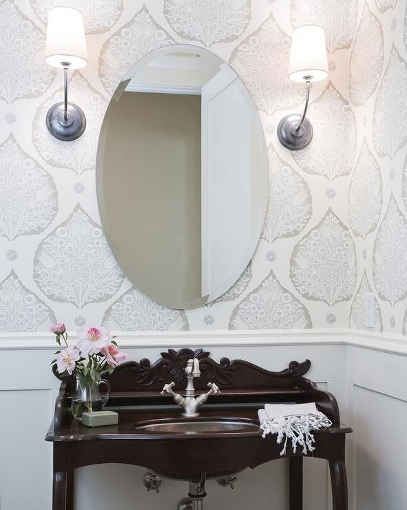 Chic powder room features top half of walls clad i…