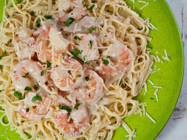 An easily adjustable recipe using alfredo sauce, cooked shrimp, canned clams, Parmesan cheese, and seasonings over fettucine pasta