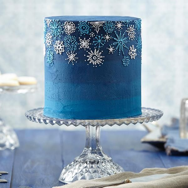 Snowfall Celebration Buttercream Cake - Celebrate snow, winter and special times with a snowflake-decorated buttercream cake. Wilton Delphinium Blue Icing Color and Sky Blue Icing Color create the deep blue dramatic background to show off the pale blue and pale violet piped snowflakes.