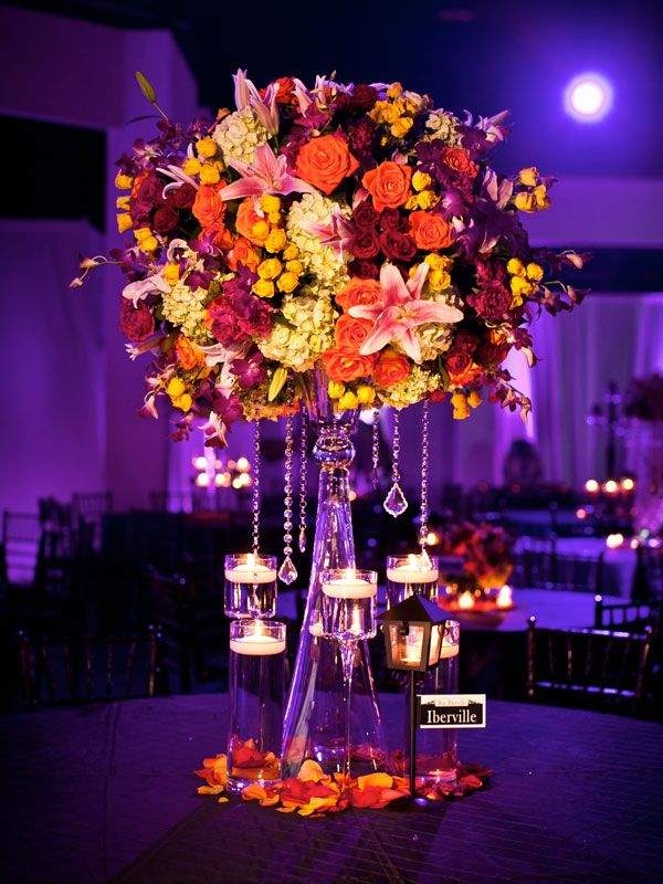 tall wedding centerpiece with yellow and orange flowers and candles...perfect for a fall wedding reception