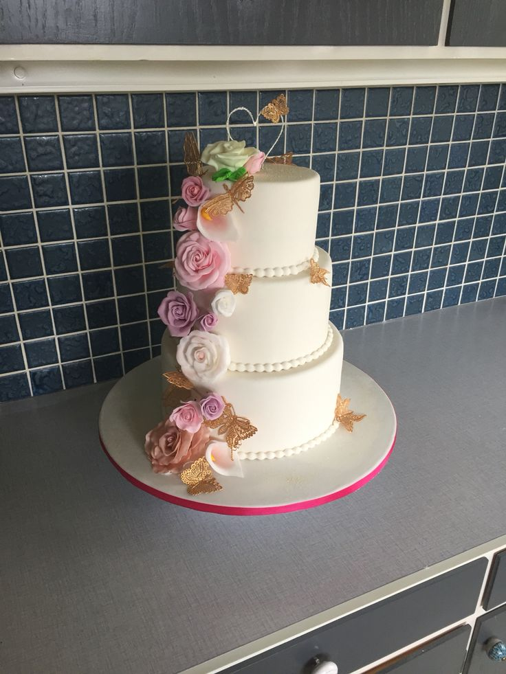 Beautiful weddingcake with three tiers, fondant roses and Claire Bowman sugarlace butterflies