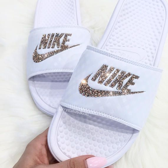 Nike Benassi Slides Made with SWAROVSKI® Crystals SELECTED STYLE: /WHITE | Width - B - Medium CRYSTAL COLOR: CRYSTAL CLEAR FIT: TRUE TO SIZE. Please see SIZE CHART in photos to confirm correct sizing. FINISH OPTION: LOGO ONLY - NIKE SIGN ONLY LOGO & NIKE - NIKE SIGN & NAME Hand customized Authentic Sneakers adored with SWAROVSKI® XIRIUS 2088 Rose-Cut Crystals. Signature pavé placement with full and even coverage and no gaps or spaces creating an unbelievable sparkle and shine.... #nike