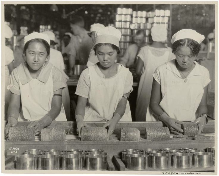 "#5 Working Conditions: ""Food––Hawaii—Canning. Native girls packing pineapple into cans""  By Edgeworth, taken for the Katakura & Company, November 20, 1928  Hawaiian pineapple canneries often employed Japanese or Filipino immigrants who worked seasonally. During the summers, when the pineapples were ripening, canneries ran two or three shifts."