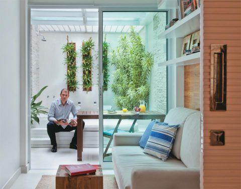 Com 13 m², o prisma interno do apartamento térreo transformou-se numa simpática área de lazer onde mesa e banheira convivem cercadas da vegetação escolhida pelo paisagista Fernando Acylino. O espaço se liga ao escritório por meio de portas de correr de vidro (1,97 x 2,16 m), que deixam a luz natural atravessar o ambiente.