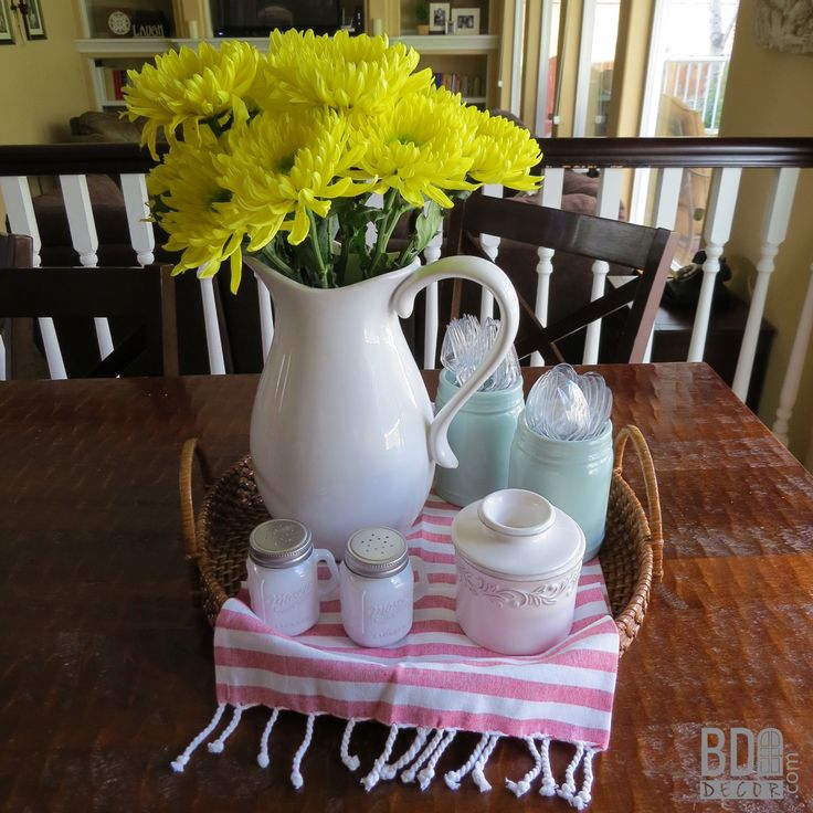 This easy everyday centerpiece starts with a basket, layers in some adorable linens, and is topped with fresh flowers and everyday USEFUL items!  Great EASY table centerpiece ideas form Blue Door Decor!