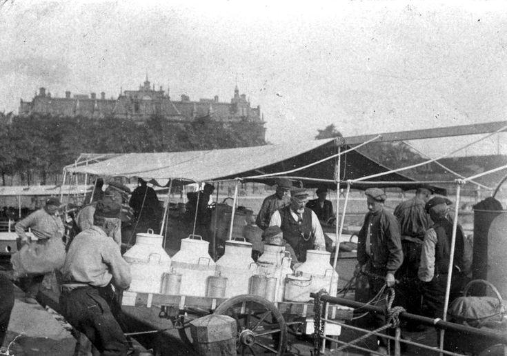 Geheugen van Nederland: 'Boeren (melkboeren) uit Noord-Holland (Waterland, Zaanstreek) brengen per boot  melk naar Amsterdam, 1911. De handkar met melkbussen wordt vanaf het schip op de kade bij de Droogbak gereden.'