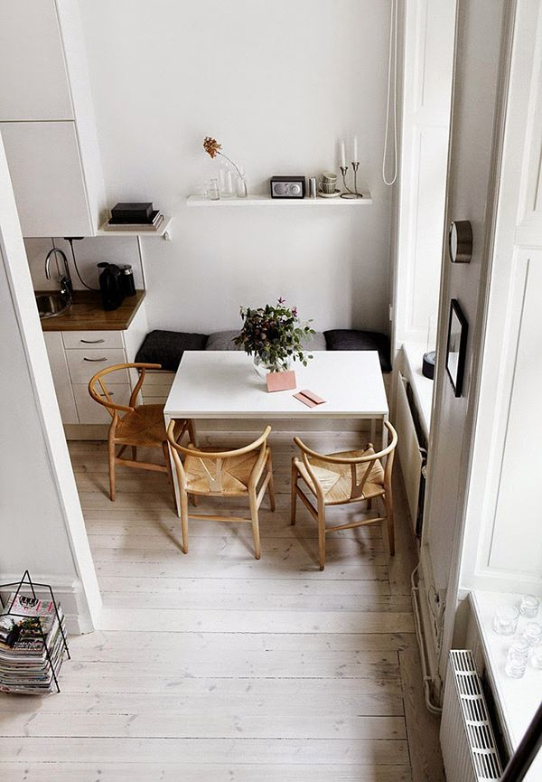 Breakfast Nook In Kitchen Banquette With Black And Grey Cushions White Dining Table Hans Wegner Wishbone Chairs Pale Limewashed Timber Floorboards