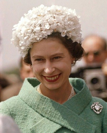 The beginning of the floral cap years: Elizabeth for this white petaled hat over a sea-green boucle, and a diamond brooch for the Epsom Derby held every June in Surrey. This year was 1962 - and it marked the Queen's 10-year anniversary on the throne.