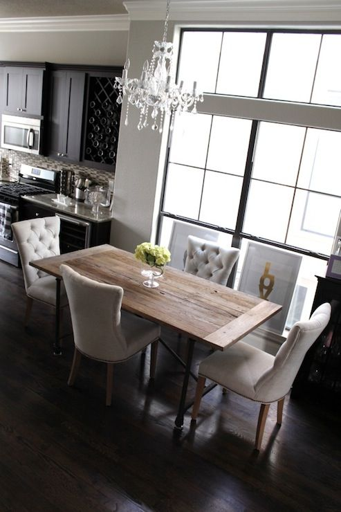 City dining room with Overstock Maria Theresa 6-light Crystal Chandelier and Made by Girl Gold LOVE Print. Dark espresso stained flooring, pale gray walls, reclaimed wood and iron dining table with tufted chairs.