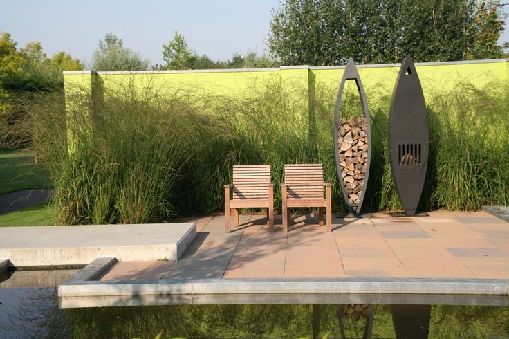 Moderne tuin met limekleur muur en houtopslag + haard.