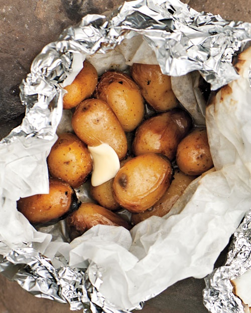 Place 1 lb baby yukon gold potatoes on a sheet of parchment-lined foil, and season with salt and pepper. Fold and crimp edges to seal, leaving an opening at the top. Pour in 1/2 cup beer (you'll have some left over). Crimp remaining edges to seal. Cook pack set over a campfire or on a medium-high grill (or nestled near coals) until potatoes are tender, 20 to 25 minutes. Top with butter
