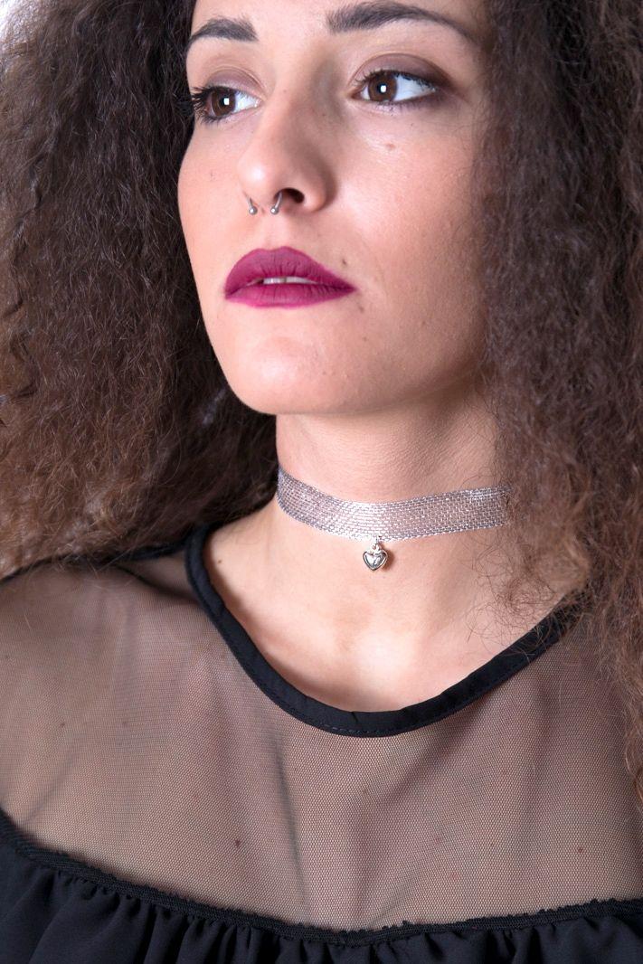 CHOKER NASTRO CUORE Choker realizzato da un intreccio metallico silver, con un piccolo cuore applicato al centro. La chiusura è caratterizzata da un dettaglio in metallo argentato. Perfettamente in linea con il trend del momento, è un accessorio elegante e raffinato.  Dimensioni: 29,5 x 1,5 cm