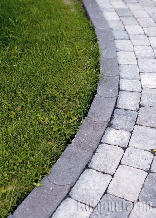 Betonireunakivi tukee kaarevaa, betonikivistä ladottua käytävää ja ehkäisee nurmikon tunkeutumista kiveykselle.