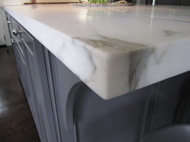 Exquisite gray kitchen island with polished nickel hardware and Grand Calacatta Gold Marble countertop.