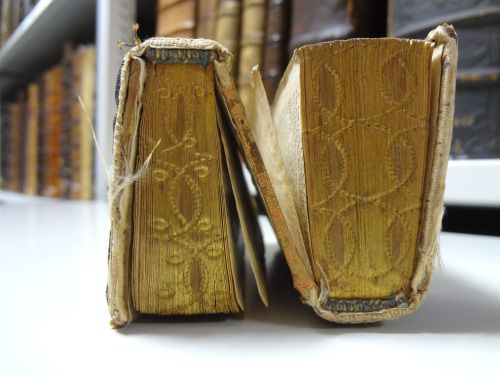 """The bookbindings are rare, called """"dos-à-dos"""" (back to back), a type almost exclusively produced in the 16th and 17th centuries. They present two different entities joint at their backs: each part has one board for itself, while a third is shared between the two. You will often find two complementary devotional works in them, such as a prayerbook and a Psalter, or the Bible's Old and New Testament. Reading one text you can flip the """"book"""" to consult the other.~ St Andrew's University Library"""