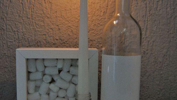 Tussen het glaswerk-afval van afgelopen feestdagen vond ik een paar potentiële accessoires in de vorm van een lege fles witte wijn en een oud kruiden potje. Eerst maar eens de etiketten eraf en goed schoonmaken. De wijnfles is daarna gedoopt in een restje witte lak, evenals de mooie champagne kurk. Het kruiden potje bleek een perfecte kaarsenstandaard. Op de achtergrond een diepe fotolijst gevuld met piepschuim.