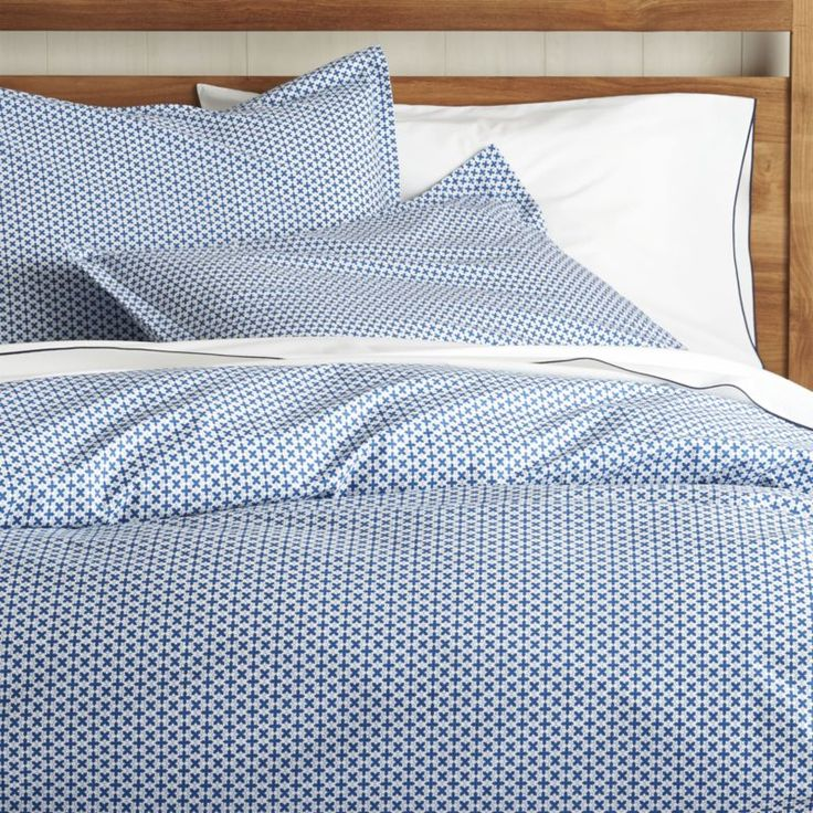 Tiny blooms lend a sweet note to our contemporary bed linens, gridded up in crisp blue and white.  Duvet has a hidden-button closure.  Shams have overlapping flap closures.  Duvet inserts and bed pillows also available. 100% cotton200-thread-countMachine wash cold; tumble dry low; warm iron as neededDo not bleachDuvet has hidden button closureShams have overlapping flap closureMade in Portugal.