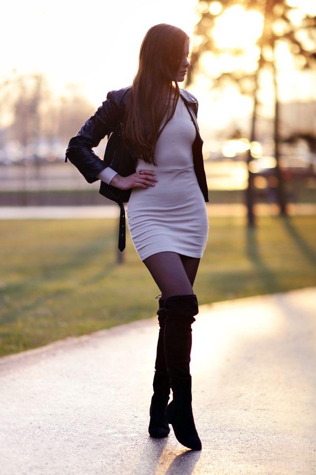 Beżowa sukienka, skórzana kurtka ramoneska, czarne rajstopy i długie kozaki