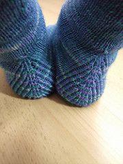 Diese Socken schmückt seitlich ein schlichtes Wellenmuster, das aber für beide Socken unterschiedlich gestrickt wird.