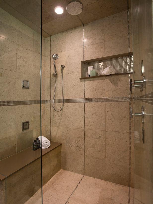 This contemporary bathroom showcases a performance shower boasting a frameless shower enclosure, built-in seat, niche and Italian floor-to-ceiling marble with stainless steel accent tiles.