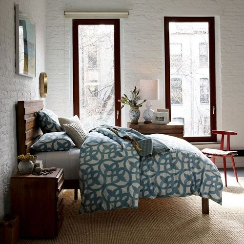 This bedroom furnished byWest Elm.  The aqua-tinged blue and stone-colored geometric bedding is all-organic cotton.