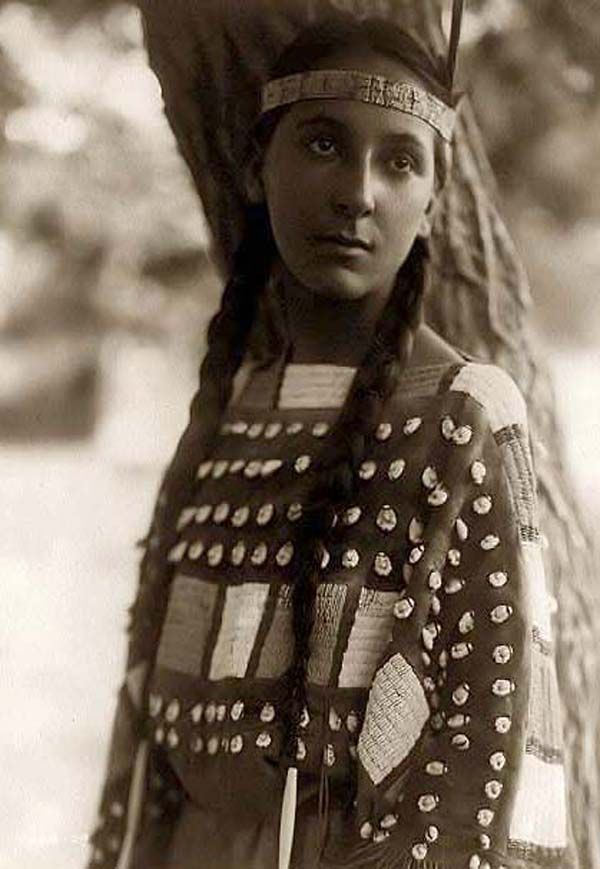 You are viewing an unusual image of Lucille, a Dakota Sioux. It was taken in 1907 by Edward S. Curtis.    The image shows a Young Native American woman in a half-length, portrait, standing, facing front.    We have created this collection of pictures primarily to serve as an easy to access educational tool. Contact curator@old-picture.com.