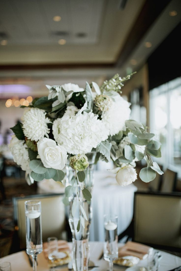 Wedding Reception Centerpieces with Tall Glass Vase with White Flowers and Greenery and Short Glass Vases with White Floating Candles | Wedding Venue Sarasota Yacht Club | Tampa Bay Wedding Planner NK Productions