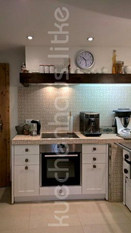Dunsthaube Eigenbau mit Holzbalken und innenliegender Entlüftung, sowie Arbeitsplatzbeleuchtung. Moderner Einbauherd neben einem alten Küchenofen ergibt einen großen Kochplatz.