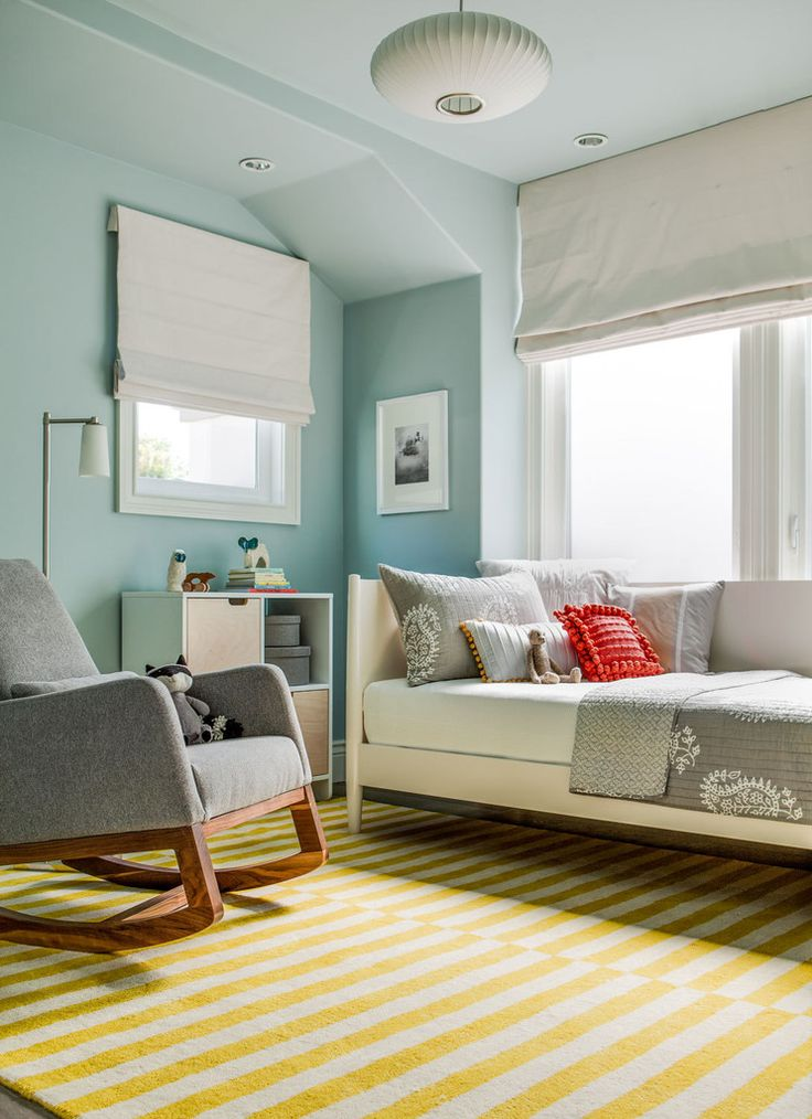 "The nursery was the one exception to the clients' restrained palette. ""We wanted this space to be more fun and saturated, but still relate to the other rooms,"" says Jones. Zero-VOC-paint color on walls, Yarmouth Blue by Benjamin Moore. Mid-Century Daybed in White, West Elm."