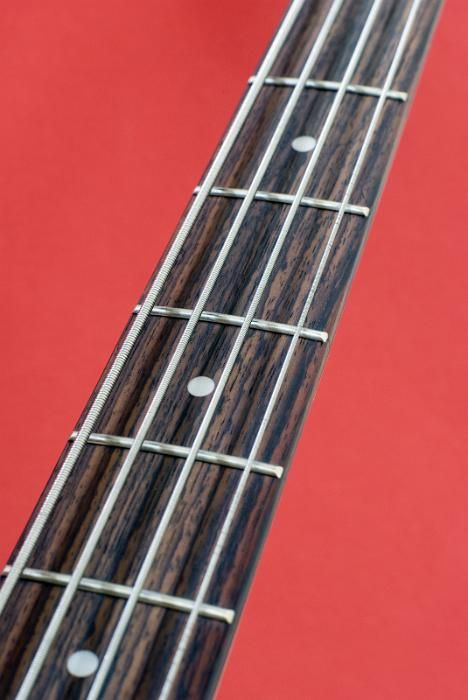 the neck, strings and frets on a bass guitar pictured against a red background - free stock photo from www.freeimages.co.uk