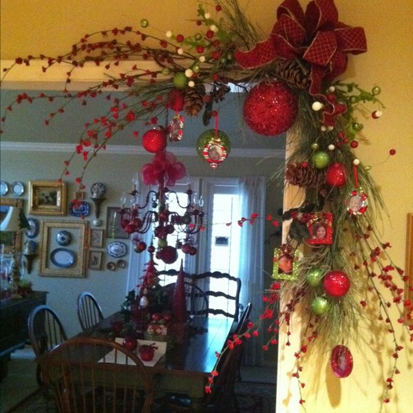 Smart! Just as festive and noticeable as a garland over the entire door, but cheaper (less materials needed), and no need to any hooks or nails in the middle of the door frame (which is more obvious than small holes in the corners).