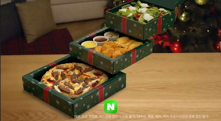 Pizza Hut Korea's Christmas Tree Boxes meal | The boxes look like green presents (complete with a red bow) and are stacked in a pyramid to resemble a Christmas tree. Meal includes a choice of a pizza & a side plus a salad topped with ricotta cheese. Pizza choices include: Cream of Chicken; Garlic Beef; Chili Seafood, Golden Potato, & Quattro Cheese. The side selection is a bit more limited with a choice of either a giant chocolate chip cookie or spicy wings & chicken tenders.