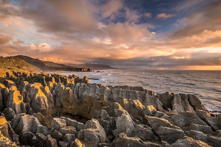 Punakaiki Pancake Rocks New Zealand | #Geology #GeologyPage #NewZealand  The Pancake Rocks are a very popular tourist destination at Dolomite Point south of the main village. The Pancake Rocks are a heavily eroded limestone area where the sea bursts through several vertical blowholes during high tides. Together with the 'pancake'-layering of the limestone (created by immense pressure on alternating hard and soft layers of marine creatures and plant sediments) these form the main attraction…