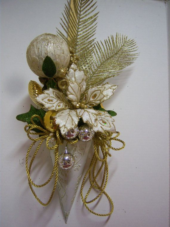 Gold and ivory holiday floral arrangement in metal wall